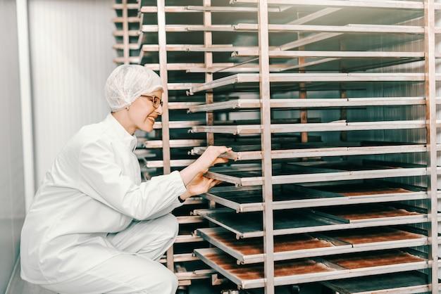 Empregado loiro caucasiano feminino jovem em uniforme estéril, colocando bandejas na prateleira enquanto agachado na fábrica de alimentos.