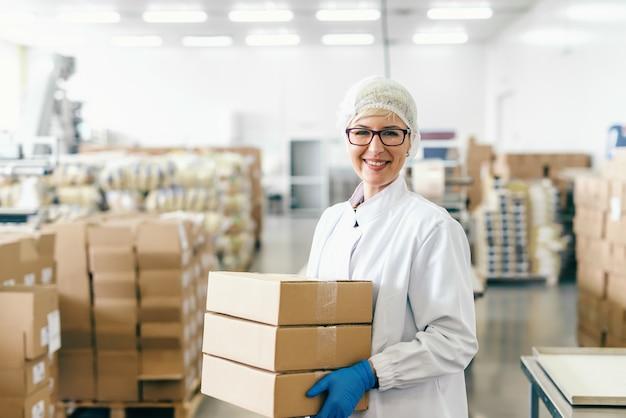 Empregado louro de sorriso no uniforme estéril e com os monóculos que guardam caixas ao estar na fábrica de alimentos.
