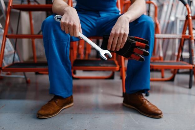 Empregado masculino uniformizado segurando uma chave inglesa na loja de ferramentas