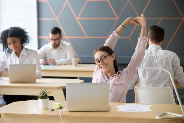 Empregado millennial, estendendo-se a pausa do trabalho de computador para relaxamento