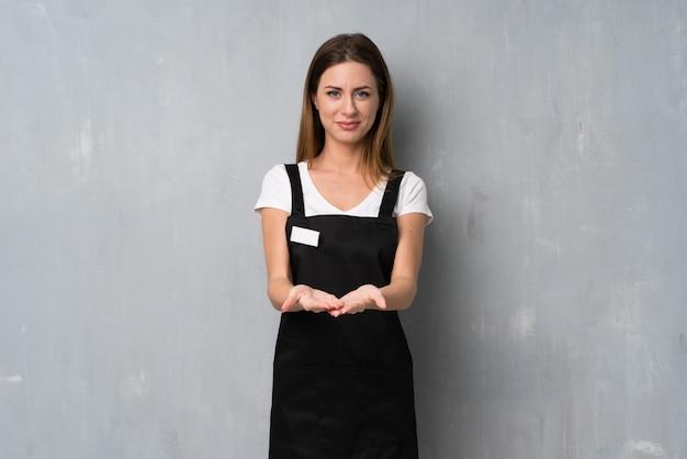 Empregado mulher segurando copyspace imaginário na palma da mão para inserir um anúncio