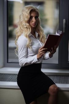 Empregado no escritório lê relatórios perto da janela, segurando um livro nas mãos