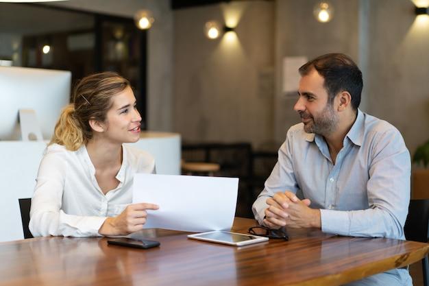 Empregado novo positivo que mostra o relatório ao colega do negócio
