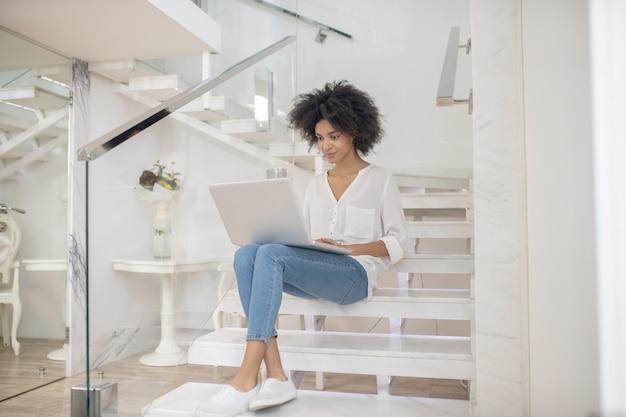 Empregado por conta própria. jovem alegre trabalhando em um laptop, sentada nos degraus de uma escada branca dentro de casa