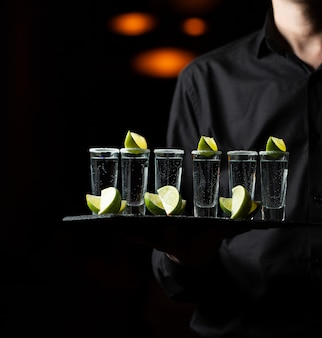 Empregado segurando uma bandeja de serviço com cocktails de limão.