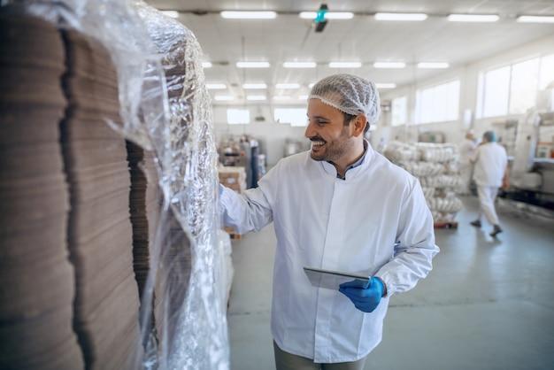 Empregado sorridente caucasiano em uniforme branco estéril usando comprimido na fábrica de alimentos.