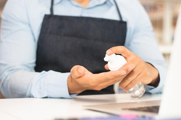 Empregado usando álcool gel para limpar as mãos para trabalhar em uma cafeteria