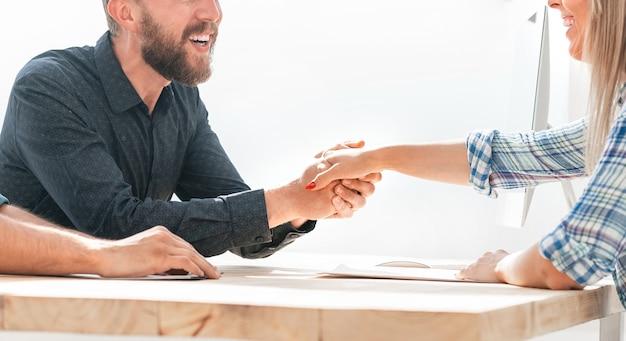 Empregador apertando a mão de um novo funcionário durante a entrevista