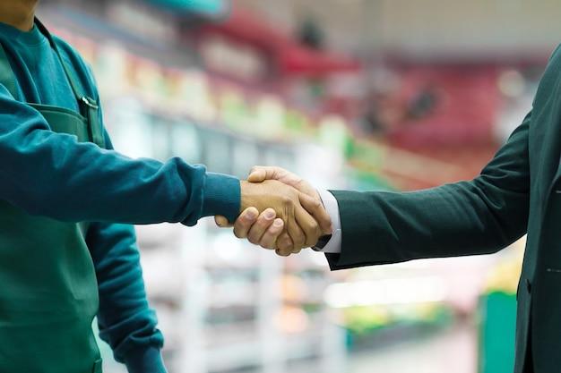 Empregador de aperto de mão de negócios e trabalhador no fundo desfocado do super mercado.