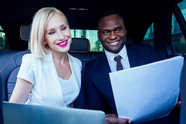 Empregador de empresário bem sucedido mulher loira com maquiagem em vestido branco de negócios com um empresário afro-americano bonito chefe em paletó preto elegante trabalhando no carro com laptop