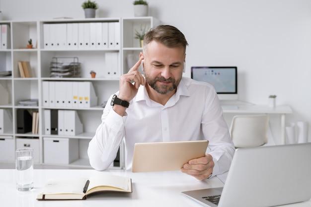 Empregador de sucesso com touchpad assistindo a vídeos online sentado na mesa em frente ao laptop