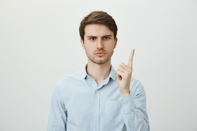 Empregador do sexo masculino decepcionado, repreendendo o trabalhador, sacudindo o dedo descontente