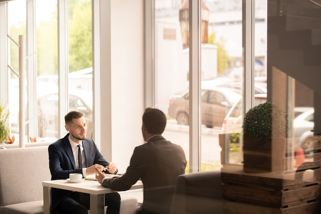 Empregador e candidato em trajes formais conversando sobre os termos de emprego enquanto estão sentados à mesa um na frente do outro