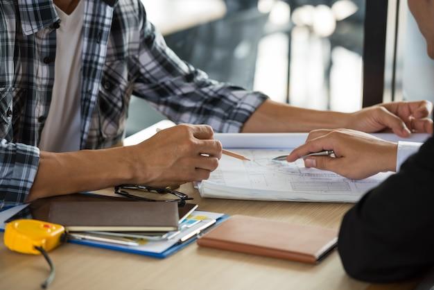 Empregador e capataz falando juntos na mesa.
