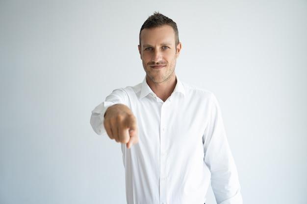 Empregador novo considerável de sorriso que aponta com o dedo na câmera ao escolhê-lo.