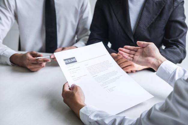 Empregador ou comitê segurando a leitura de um currículo falando durante o seu perfil de candidato.