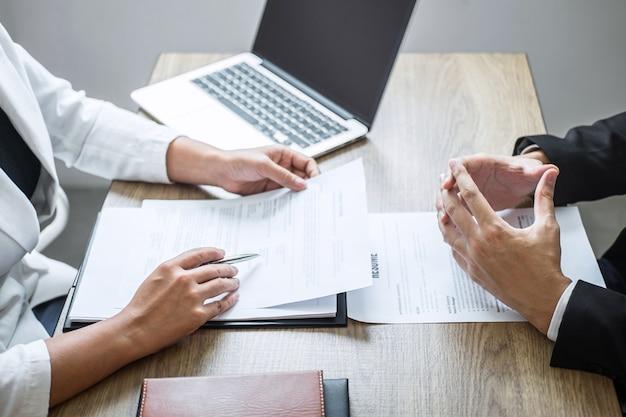 Empregador ou recrutador segurando a leitura de um currículo com a falar durante o seu perfil de candidato, o empregador de terno está conduzindo uma entrevista de emprego, emprego de gerente de recursos e conceito de recrutamento