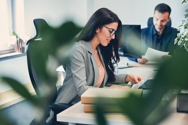 Empregadora autoconfiante usando óculos, trabalhando no novo escritório usando um computador moderno