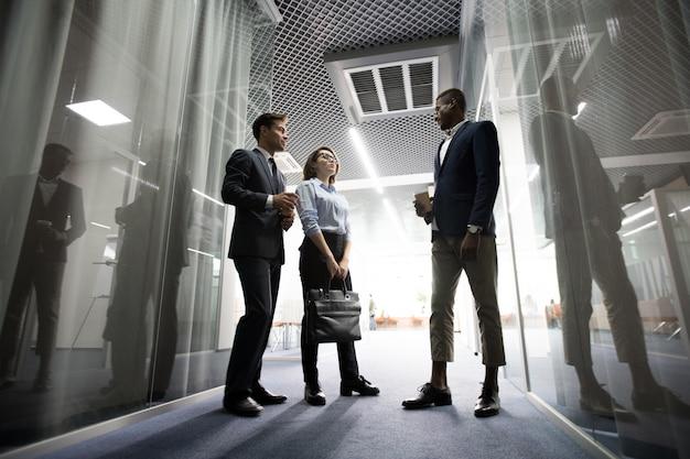 Empregados de negócios pensativo tomando café no corredor do escritório