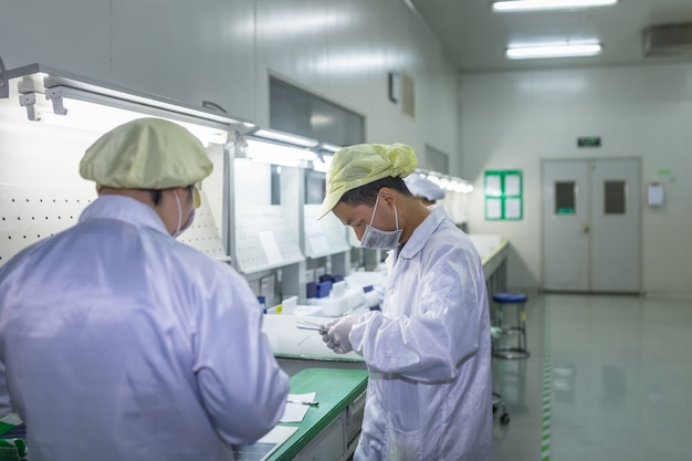 Empregados em roupas de proteção trabalham em fábricas limpas