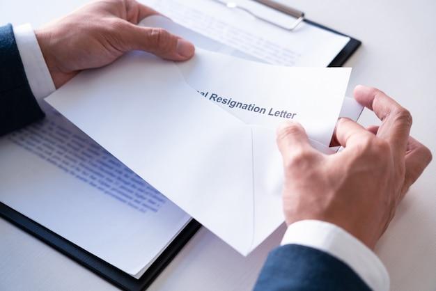 Empregados que pretendem sair do trabalho com cartas de demissão por desistência ou mudança de emprego que saem do escritório, desemprego, conceito de demissão