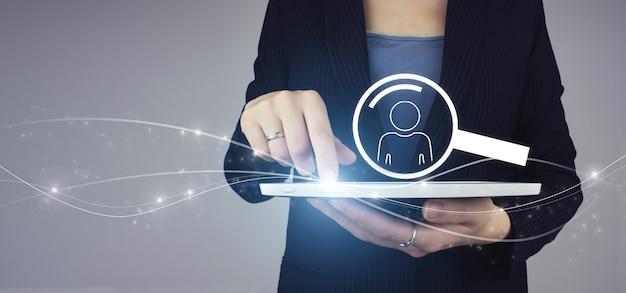 Emprego de recrutamento de recursos humanos de rh. tablet branco na mão da mulher de negócios com holograma digital humano, sinal de ícone de líder em fundo cinza. pesquisa humana. líder e ceo.