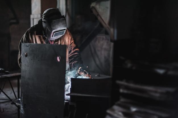 Emprego de um soldador. uma grande fábrica de produtos de concreto e soldagem sobre ela.