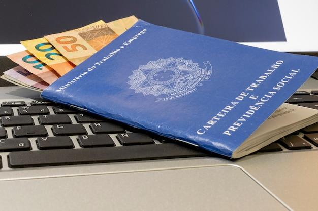 Emprego e conceito de controle financeiro com contas de dinheiro brasileiras e cartão de trabalho no teclado