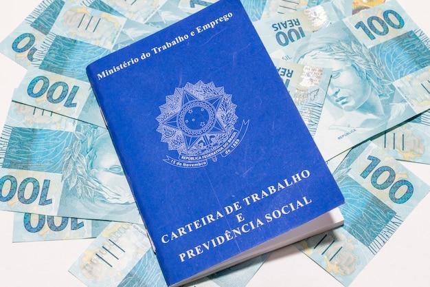 Emprego e conceito de controle financeiro com notas de dinheiro e carteira de trabalho brasileira.