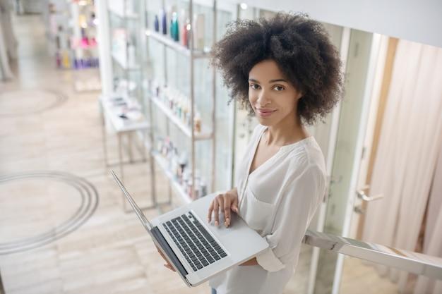 Emprego, sucesso. jovem sorridente com cabelo encaracolado com laptop aberto na escada interna com maquiagem