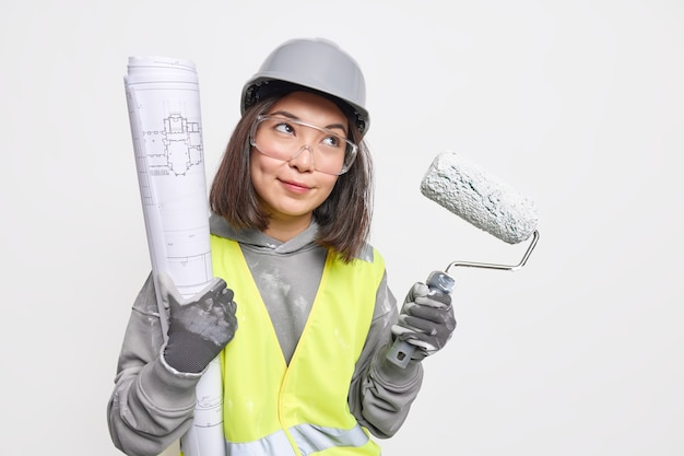 Empreiteira atenciosa olha para a distância segura o rolo de pintura e o projeto desenvolve ew usa capacete de proteção, óculos de proteção, colete de segurança reflexivo
