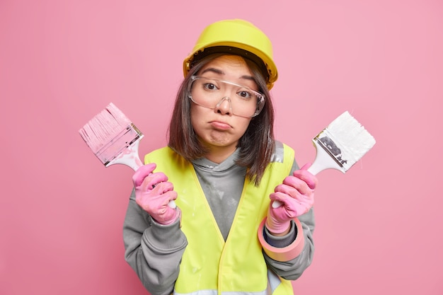 Empreiteira segura dois pincéis de pintura nas mãos bolsas lábios prontos para pintar paredes internas usa capacete de segurança óculos transparentes e uniforme