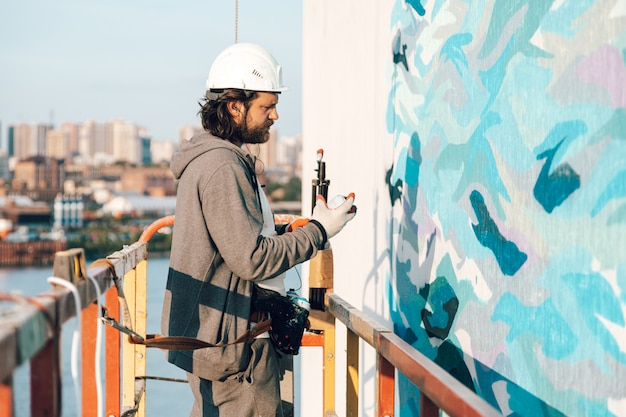 Empreiteiro, artista em alta altitude em um berço de edifício realiza pintura de fachada, decoração e reforma da casa