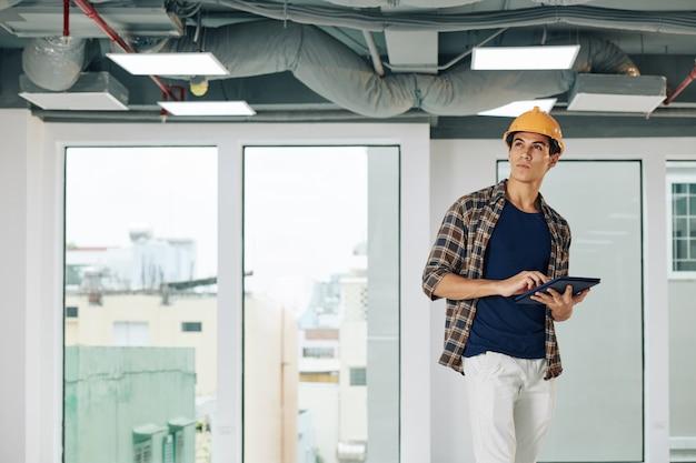 Empreiteiro com tablet digital inspecionando casa e verificando canos e fios no teto