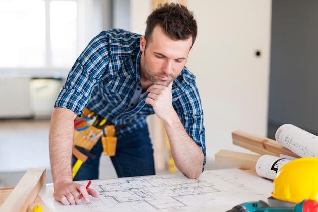 Empreiteiro de construção debruçado sobre plantas residenciais