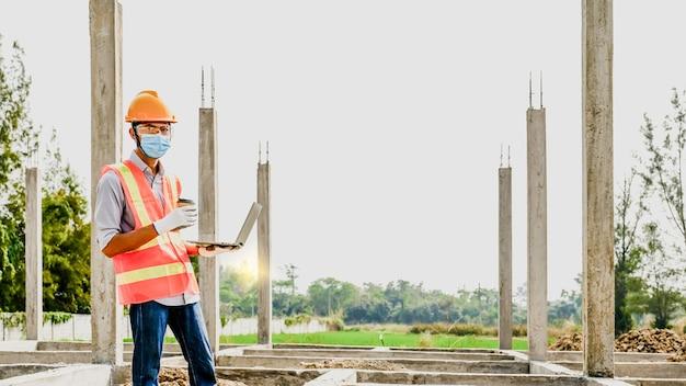 Empreiteiro de engenharia usa projeto de plano de verificação de projeto de indústria de trabalho de laptop no canteiro de obras