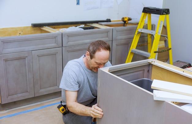 Empreiteiro de melhorias instalando novos armários de cozinha personalizados, decoração de móveis, novos armários