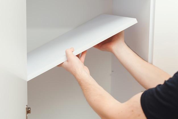 Empreiteiro de reparos montando móveis novos em apartamento moderno