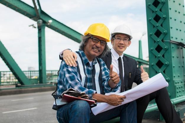 Empreiteiro e engenheiro de construção sentado e mostrando o polegar para admirar na construção