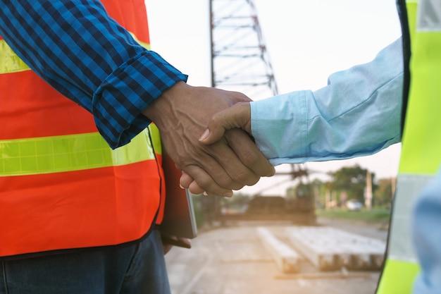 Empreiteiros e engenheiros juntam as mãos para concordar em trabalhar juntos. construção, de, edifícios, conceito