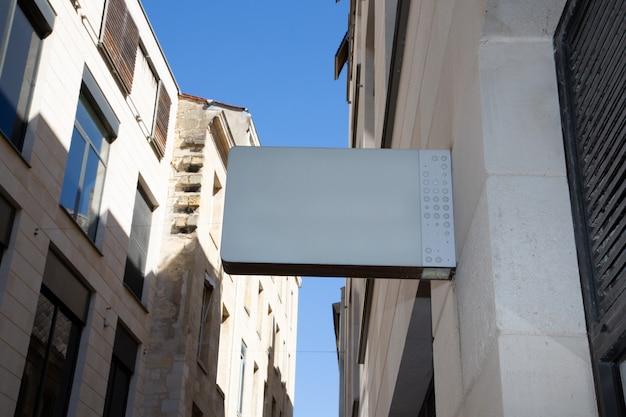 Empresa branca em branco placa de sinal loja simulada acima na parede da cidade rua