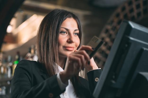 Empresa de pequeno porte, pessoas e conceito do serviço - mulher ou garçom ou gerente feliz no avental no balcão com a caixa que trabalha no bar ou na cafeteria