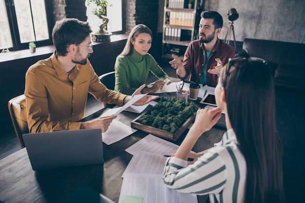 Empresa de quatro bons ocupados, profissionais, empresários, gerente, corretor, agente, sentado à mesa, discutindo estratégia
