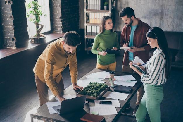Empresa de quatro simpáticos gerentes de negócios inteligentes, inteligentes e ocupados preparando um plano estratégico de inicialização de imóveis financeiros