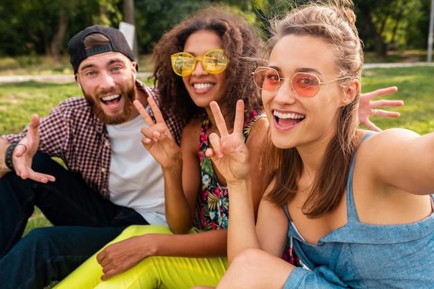Empresa jovem e elegante e colorida de amigos sentados no parque, homens e mulheres se divertindo juntos