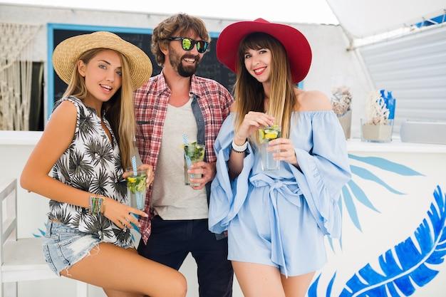 Empresa jovem hippie de amigos de férias em um café de verão, bebendo coquetéis de mojito