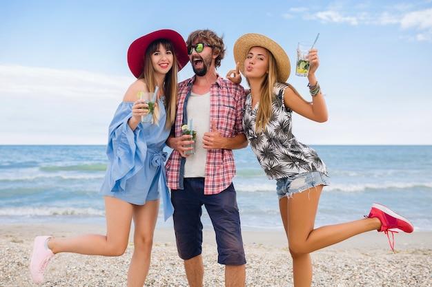 Empresa jovem hippie de amigos de férias na praia, bebendo coquetel de mojito, feliz positivo, estilo verão, sorrindo feliz, duas mulheres e um homem se divertindo juntos, conversando, flertando, romance, três