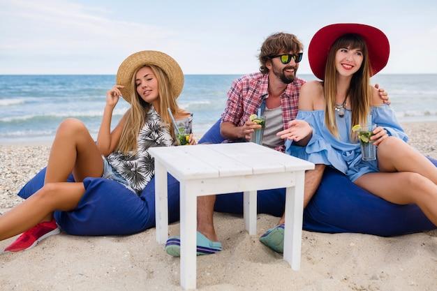 Empresa jovem hippie de amigos de férias no café da praia, bebendo coquetel mojito, feliz positivo, estilo de verão, sorrindo, feliz, duas mulheres e um homem se divertindo juntos, conversando, namorando, romance, três