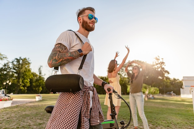 Empresa jovem hippie de amigos se divertindo juntos no parque, sorrindo, ouvindo música no alto-falante sem fio