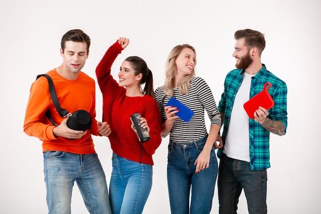Empresa jovem hippie de amigos se divertindo juntos, sorrindo, ouvindo música em alto-falantes sem fio, dançando rindo na parede branca isolada com roupa colorida e elegante